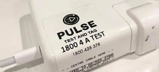 a phone charger with a pulse test and tag test sticker on it